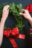 Mãos do florista que fazem a grinalda do Natal Imagens de Stock