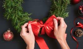 Mãos do florista que fazem a grinalda do Natal Fotos de Stock