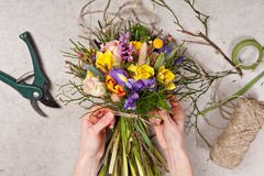 Mãos do florista que fazem o ramalhete saltar flores Fotos de Stock