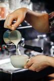 Mãos do garçom que derramam o leite que faz o cappuccino fotos de stock royalty free