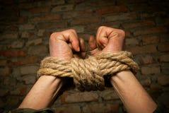 Mãos do homem amarradas acima com corda imagens de stock royalty free