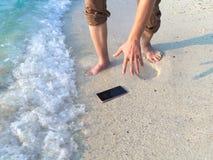 Mãos do homem asiático novo que deixa cair o telefone esperto móvel no Sandy Beach tropical Conceito do acidente e dos equipament imagem de stock royalty free