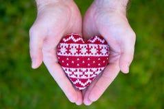 Mãos do homem com coração feito malha vermelho Fotos de Stock