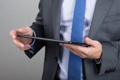 Mãos do homem de negócio que guardam o PC da tabuleta Fotos de Stock