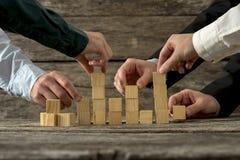 Mãos do homem de negócios cinco que guarda os blocos de madeira que colocam os int Fotografia de Stock