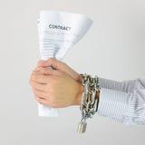 Mãos do homem de negócios com correntes e contrato Imagem de Stock