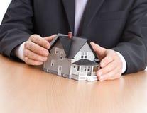 Mãos do homem de negócios em torno do modelo arquitectónico fotos de stock royalty free