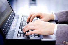 Mãos do homem de negócios no teclado do caderno Fotos de Stock Royalty Free