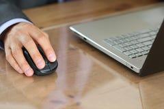 Mãos do homem de negócios no terno que guarda o rato do rádio do computador Foto de Stock
