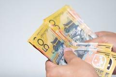 Mãos do homem de negócios que contam o isolado australiano de cinqüênta notas de dólar imagem de stock royalty free
