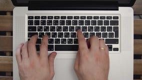 Mãos do homem de negócios que datilografam no laptop Fim acima tiro 4k Vista superior video estoque