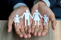 Mãos do homem de negócios que guardam o papel da família fotos de stock royalty free
