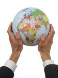 Mãos do homem de negócios que prendem o globo fotografia de stock royalty free