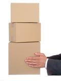 Mãos do homem de negócios que prendem pacotes Fotografia de Stock
