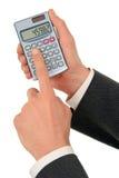 Mãos do homem de negócios que prendem uma calculadora foto de stock royalty free