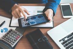 Mãos do homem de negócios usando a informação do texto na tabuleta digital ao imagem de stock royalty free