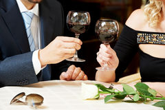 Mãos do homem e da menina com vinho no café em uma tâmara Fotografia de Stock Royalty Free