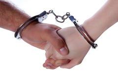 Mãos do homem e da mulher com algemas Fotos de Stock Royalty Free