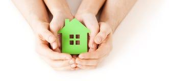 Mãos do homem e da mulher com a casa do papel verde Foto de Stock Royalty Free