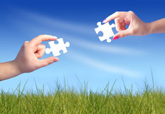Mãos do homem e da mulher com enigmas Foto de Stock