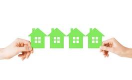 Mãos do homem e da mulher com muitas casas do papel verde fotografia de stock