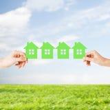 Mãos do homem e da mulher com muitas casas do papel verde Imagens de Stock