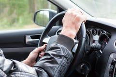 Mãos do homem na roda de carro foto de stock royalty free