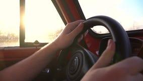 Mãos do homem na roda de pouca movimentação retro vermelha do carro no fim da estrada acima do tiro vídeos de arquivo