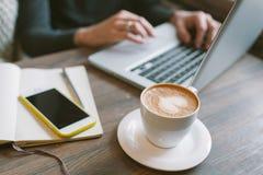 Mãos do homem no portátil com café e smartphone com bloco de notas Imagens de Stock Royalty Free