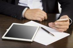 Mãos do homem no terno de negócio na mesa com papéis e dispositivos eletrónicos Fotografia de Stock Royalty Free
