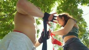 Mãos do homem novo e da mulher que envolvem as mãos com as ataduras para o exercício no dia de verão video estoque