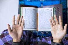 Mãos do homem novo que rezam ao Allah fotografia de stock