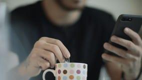 Mãos do homem novo usando o telefone celular na manhã Homem de neg?cios que guardara o telefone video estoque