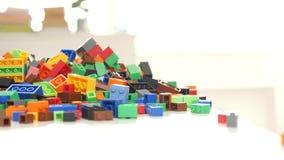 Mãos do homem que abrem uma caixa com os tijolos plásticos pequenos coloridos para construções do brinquedo video estoque