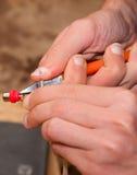 Mãos do homem que cortam o fio do conector Fotografia de Stock