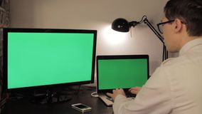 Mãos do homem que datilografam no laptop verde da tela vídeos de arquivo