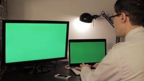 Mãos do homem que datilografam no laptop verde da tela video estoque