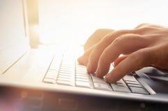 Mãos do homem que datilografam no teclado do portátil