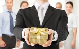 Mãos do homem que guardam a caixa de presente no escritório imagens de stock