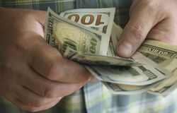 Mãos do homem que guardam o dinheiro Imagem de Stock