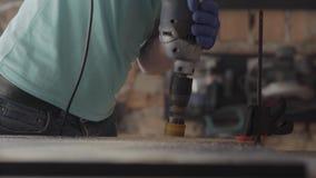 Mãos do homem que parafusam o furo com a ferramenta no MDF do fim de madeira da placa acima Fabrica??o da mob?lia Processo de tra video estoque