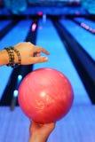 Mãos do homem, que prende a esfera no clube do bowling fotografia de stock royalty free