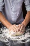 Mãos do homem que preparam a massa do pão Imagem de Stock