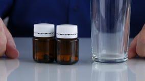 Mãos do homem que preparam uma cura médica com comprimidos e um vidro para a água filme