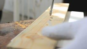 Mãos do homem que usa o perfurador bonde para girar o parafuso à madeira filme