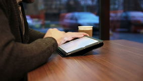 Mãos do homem usando o écran sensível da tabuleta no café video estoque