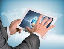 Mãos do homem usando o PC da tabuleta Imagem da terra sobre Imagens de Stock
