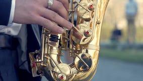 Mãos do jogo do noivo no saxofone Mãos do close up do homem que jogam o saxofone dourado do alto com efeito da luz Jogo dos homen fotos de stock