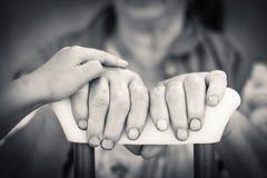 Mãos do jovem superior e que guardam a muleta Fotografia de Stock Royalty Free