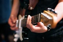 Mãos do músico guitarra preta no fundo borrado foto de stock